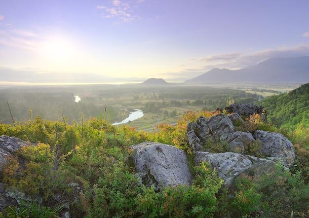 Каменистый склон горы на фоне холмов в тумане в долине реки катуни