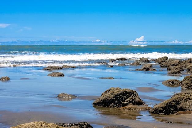 푸른 하늘 아래 바위 해변 풍경 보기