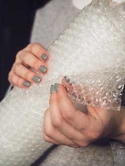 女性の手にプチプチのロール。フィルムを使用した壊れやすいアイテムの信頼性の高いパッケージング。