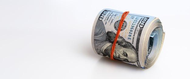 Рулон долларов на белом фоне сто американских долларовых купюр