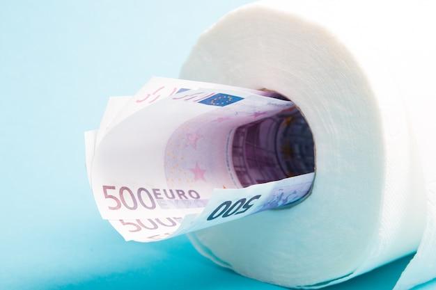 Рулон туалетной бумаги и банкноты евро