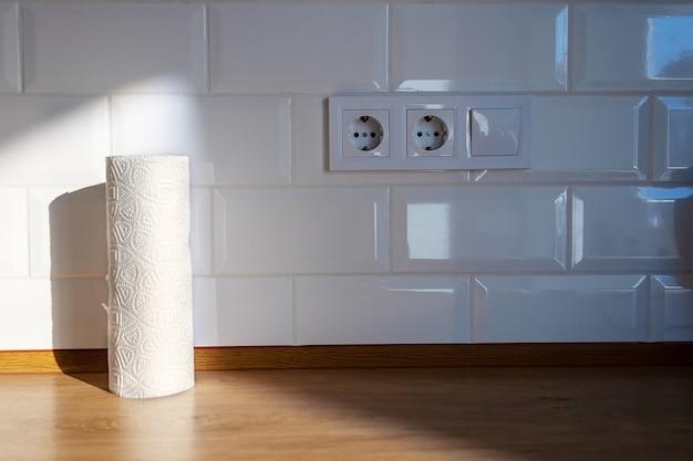 흰색 무늬가 있는 주방용 종이 타월 롤은 흰색 타일 벽에 기대어 있는 나무 조리대 위에 햇빛 아래 서 있고 옆에는 유럽 콘센트 2개와 스위치가 있습니다.