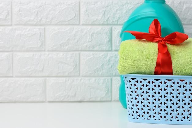 욕실의 흰색 선반에 빨간 실크 리본과 액체 세탁 분말 플라스틱 병으로 묶인 롤업 테리 녹색 수건