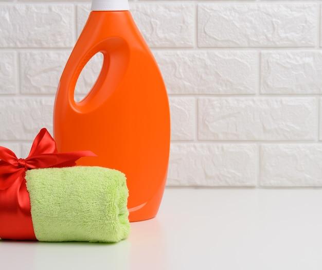 Свернутое махровое зеленое полотенце, перевязанное красной шелковой лентой, и оранжевая пластиковая бутылка жидкого стирального порошка на белой полке в ванной комнате.