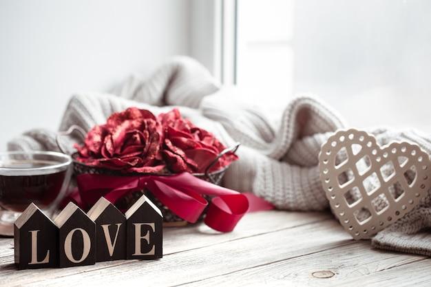Романтическая композиция на день святого валентина с декоративным словом love и деталями декора.