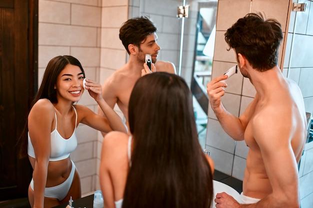 욕실에서 로맨틱 커플. 한국 여성이 면봉을 사용합니다. 남자는 면도기를 사용합니다. 아침 루틴. 얼굴 피부 관리. 위생.