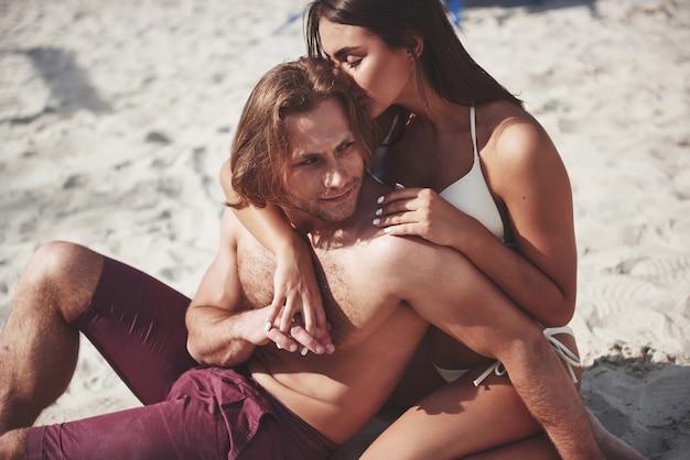 ビーチで水着でロマンチックなカップル、美しいセクシーな若者。