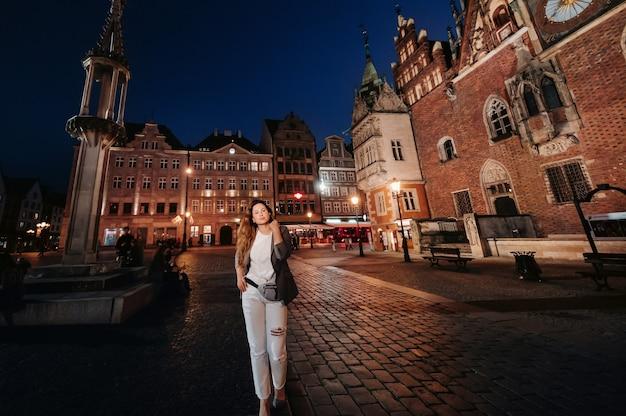 ロマンチックな女の子が夜遅くにヴロツワフの旧市街を歩きます。ポーランドの旧市街でズボンとジャケットを着た女性の散歩。