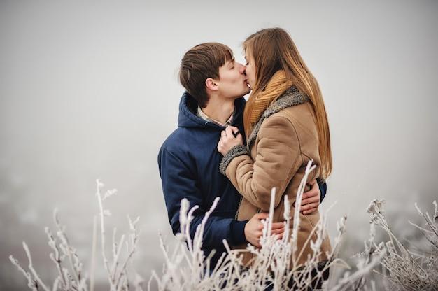 Романтическая влюбленная пара гуляет в снежном парке. зимние каникулы. мужчина и женщина обнимаются и целуются, наслаждаясь прогулкой.