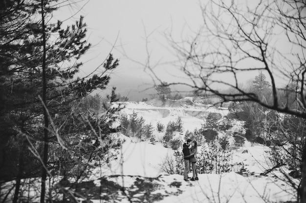Романтическая влюбленная пара гуляет в снежном парке.