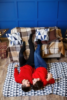 ロマンチックな瞬間。赤いセーターを着たカップルが抱き合ってキスをして床に横たわっている