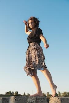 海の石の上でポーズをとる黒いtシャツとスカートを着た巻き髪の女性のロマンチックな散歩