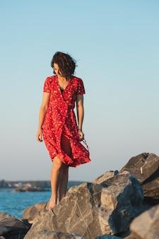 海の石の上でポーズをとって赤いドレスの巻き毛の女性のロマンチックな散歩
