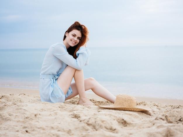 투명한 파란 드레스를 입은 로맨틱 한 여인이 바다 근처의 모래 위에 앉아 미소 짓는다.