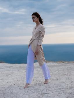 薄着のロマンチックな女性が壁の砂と海の上を歩く