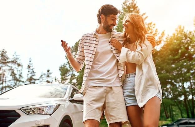 Романтичная молодая влюбленная пара обнимается возле машины. кемпинг, выходные. отдых, путешествия, концепция туризма.