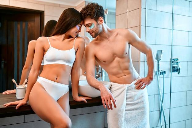 욕실에있는 로맨틱 한 젊은 부부는 눈 밑에 보습 패치를 붙여서 얼굴을 만지면 서 즐겁게 지냅니다. 아침 루틴, 얼굴 피부 관리.