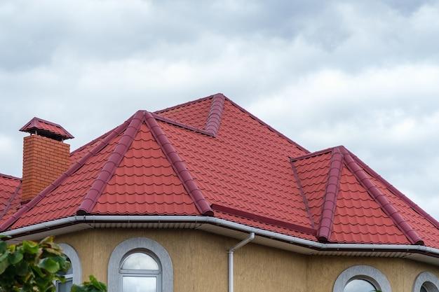 흐린 하늘을 배경으로 굴뚝이 있는 빨간 금속 타일로 만든 지붕.