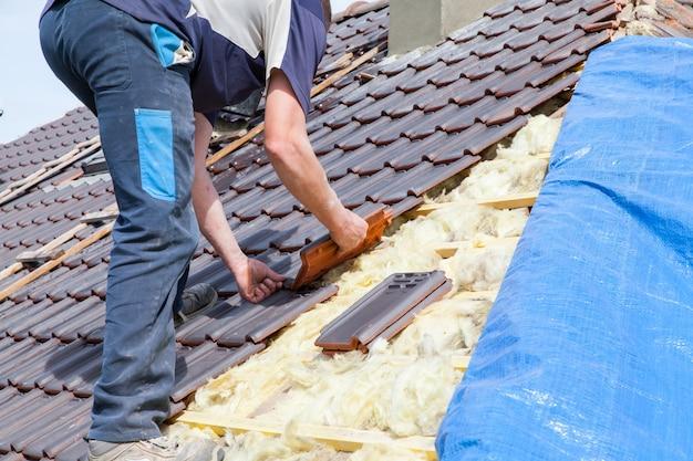 Кровельщик укладывает плитку на крышу