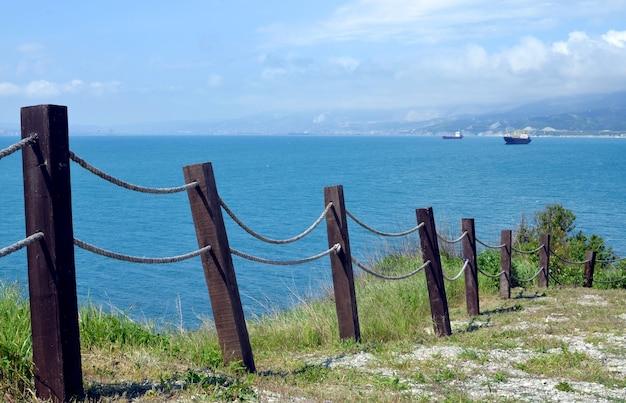 海、船、山、街を望むロープフェンス。沿岸柵。