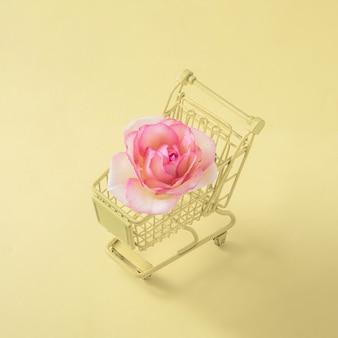 パステルイエローの背景に店のカートのバラ。最小限の創造的なコンセプト。花を買う。