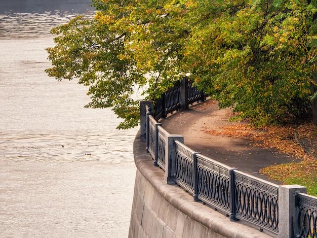 秋の大きな木の枝を持つ都市の川の堤防の丸い断片。