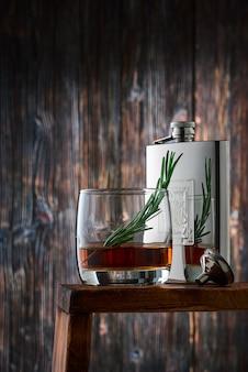 ウイスキーのショットとローズマリーの小枝が付いた丸いグラス