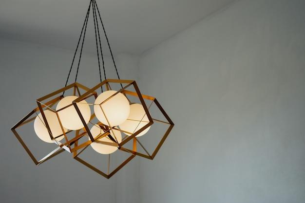 천장에 매달린 직사각형 철제 프레임이 있는 둥근 램프로 금빛으로 빛납니다. 인테리어 컨셉입니다.
