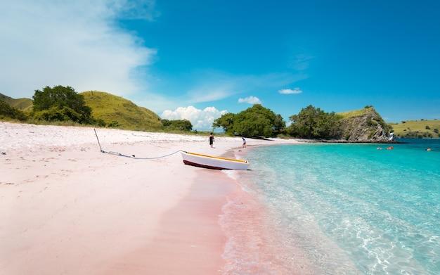 Яркая лодка на розовом пляже с бирюзовой прозрачной водой на острове комодо