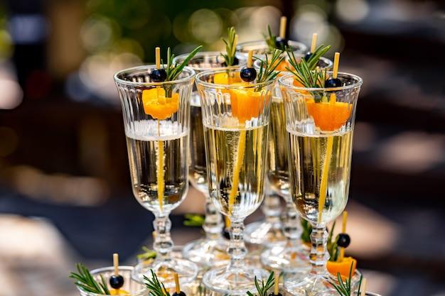 샴페인 잔의 행입니다. 배경이 흐릿한 선택적 초점입니다. 결혼식에서 뷔페 테이블입니다. 확대.