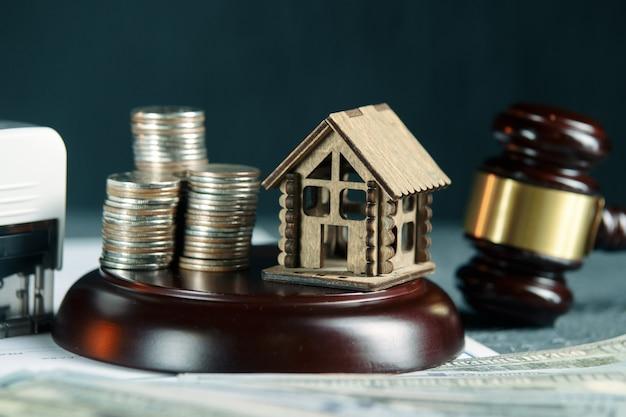Ряд монет на модели небольшого дома и молоток законного аукциона
