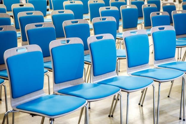 Ряд пустых синих стульев в аудитории.