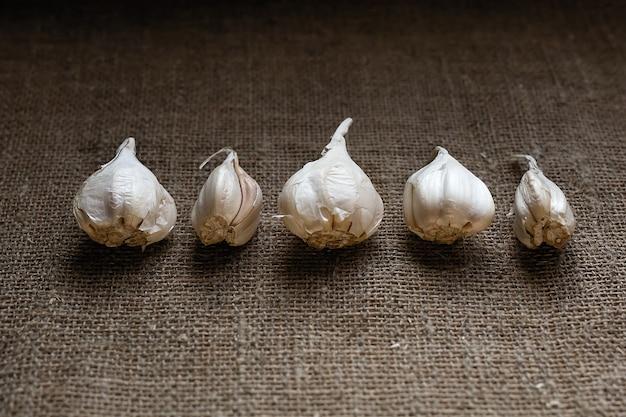 구근과 정향을 곁들인 신선한 마늘 행이 어두운 키의 삼베 위에 테이블에 놓여 있습니다.