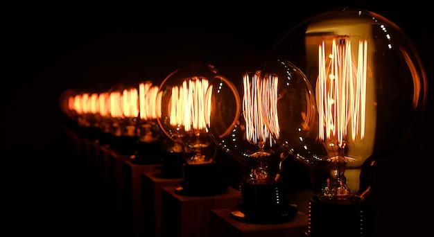 Ряд ретро стеклянные лампы на темном фоне, крупным планом. дизайнерский свет и освещение в интерьерах. выборочный фокус.