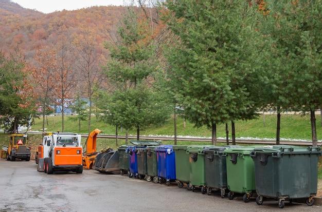 Ряд мусорных баков. техника уборки городских улиц.