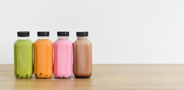 白い色の背景を持つ木製のテーブルの上のペットボトルの様々なボブルティーの列