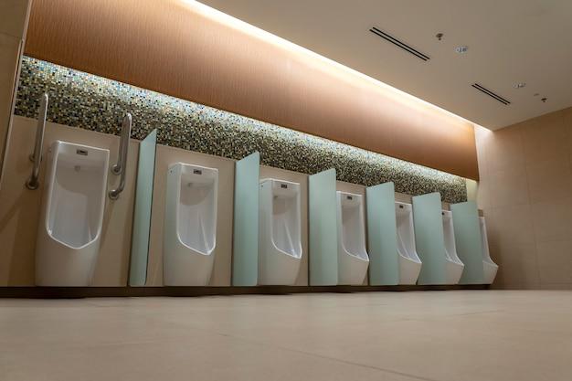 公衆トイレのタイル張りの壁に白い小便器が並んでいます。空の男のトイレ