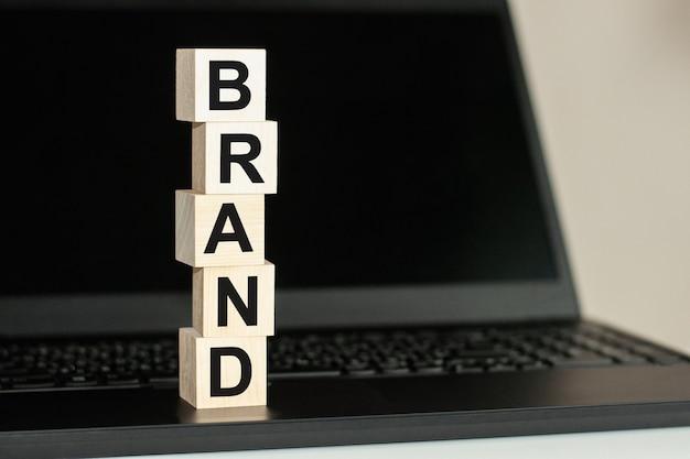 검은 색 글꼴로 쓰여진 브랜드라는 단어가있는 나무 큐브 행이 검은 색 키보드에 있습니다.
