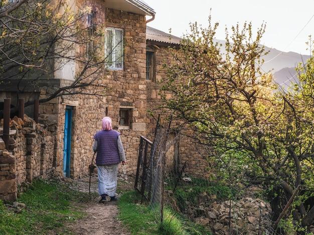 田舎の女性が山の村を歩きます。後ろからの眺め。ダゲスタン。ゴール。
