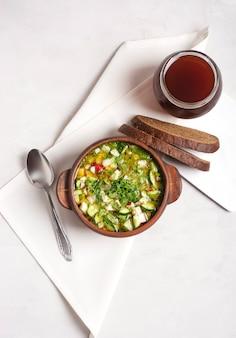 粘土のカップに新鮮な野菜と肉を入れたロシアのオクローシカが灰色の上に立っています