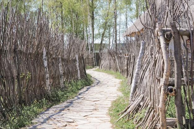 돌로 포장된 소박한 길과 나뭇가지의 천연 소재로 만든 나무 울타리. 자연과 플라스틱의 생태를 돌보는 것. 러시아 시골 마을