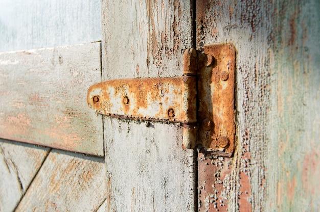 오래 된 판자 문에 녹슨 빈티지 철강 도어 잠금.