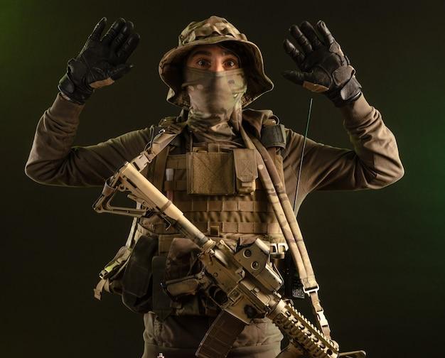 어두운 배경에 무기를 든 군복을 입은 파괴자 군인이 손을 들고 항복한다