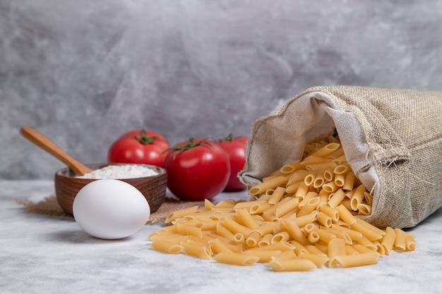 빨간 토마토와 밀가루를 곁들인 말린 펜네 이탈리아 파스타로 가득 찬 자루 가방