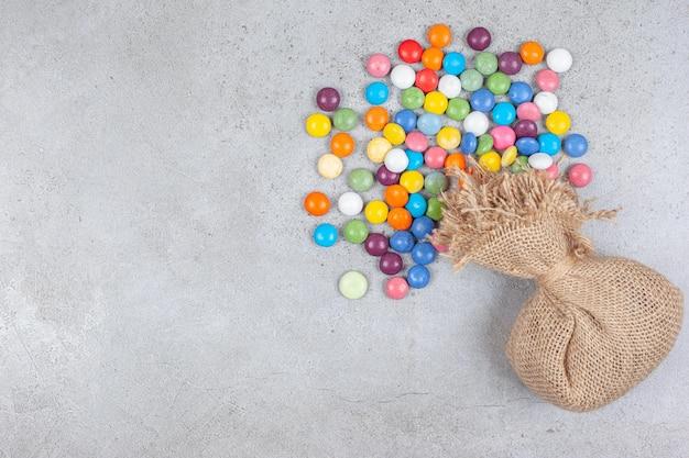 Мешок с букетом конфет, разбросанных рядом на мраморном фоне. фото высокого качества