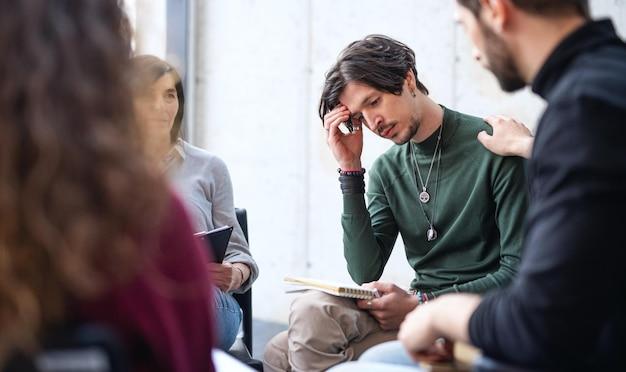그룹 치료에 원 안에 앉아 있는 슬프고 우울한 남자, 그를 지지하는 다른 사람들.