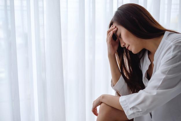 침실에 혼자 앉아 슬프고 스트레스 젊은 아시아 여성