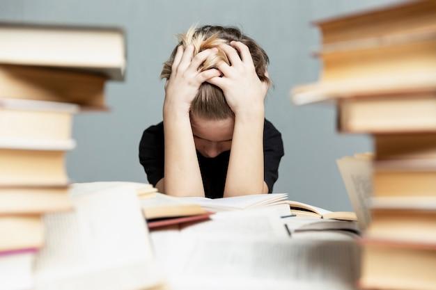 ストレスの多い9-10歳の悲しい少年は、本を持ってテーブルに座り、頭の後ろで手を共有します。灰色の背景。試験と学習障害。