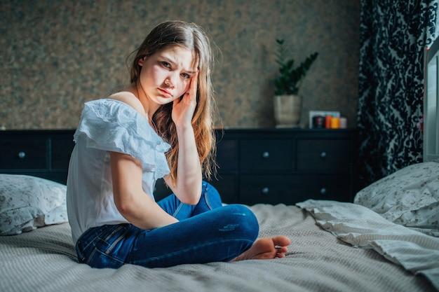 Грустная темноволосая девушка в белой блузке и синих джинсах сидит на кровати в своей спальне. у нее болит голова.