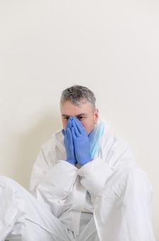 Грустный врач в защитном костюме сидит на полу в коридоре больницы. медицинские работники во время пандемии коронавируса covid19.